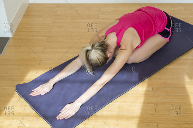 blond young woman wearing pink top and black shorts stretches her arms while face down on a yoga mat and wooden floor