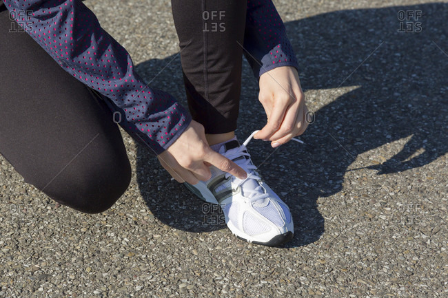 Athletic young woman bending down in a rural road tying her shoe laces as she pauses during her daily run looking at the camera with a lovely friendly smile