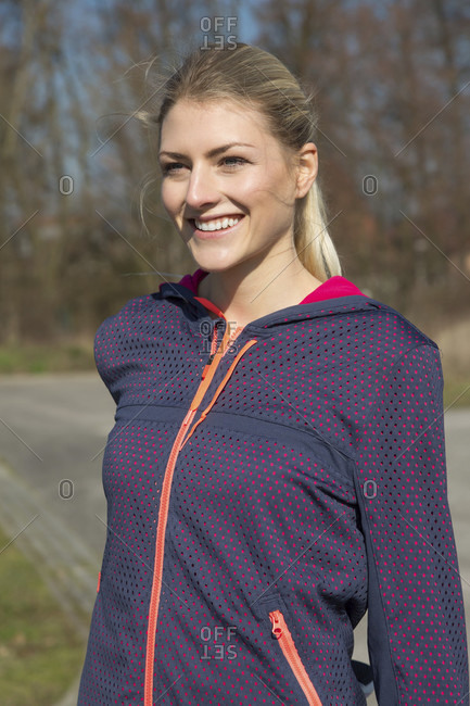 Young woman stretching to warm up her muscles as she stands outdoors alongside a rural road with woodland ready to go for her morning jog, upper body smiling at camera