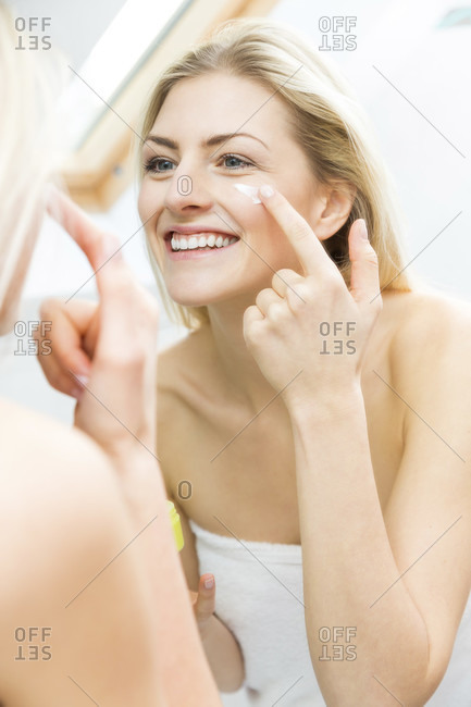 Pretty young woman wrapped in a white towel standing smiling in front of the mirror applying a cream or moisturizer to her face in a skincare and beauty concept