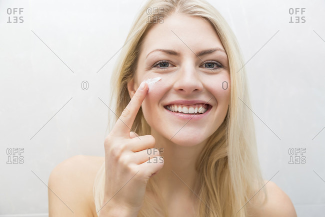 Single smiling woman applying cream to face