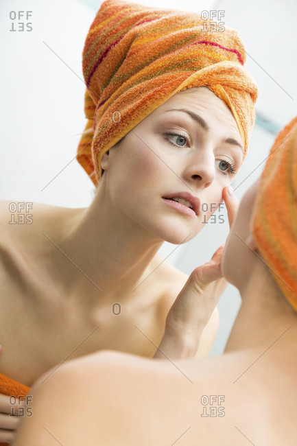 Attractive woman wrapped in towel touching the sides of her face with big happy smile in reflection on mirror
