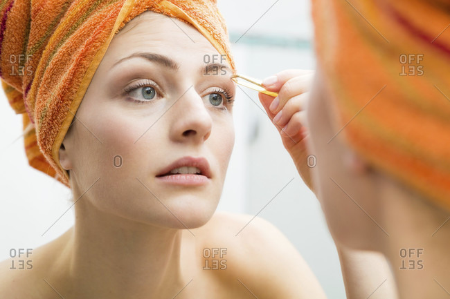 Pretty woman with her hair wrapped in an orange towel plucking her eyebrows with tweezers looking at her reflection in the mirror in a beauty portrait