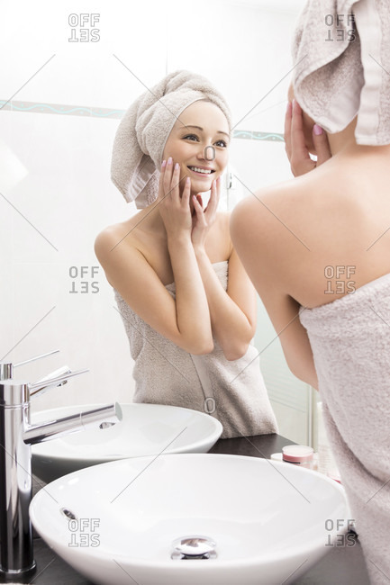 Portrait of Young Woman Smiling at Reflection of Self in Bathroom MirrorYoung Woman Wrapped in Towels After Shower and Touching Face with Hands and Looking at Self in Mirror