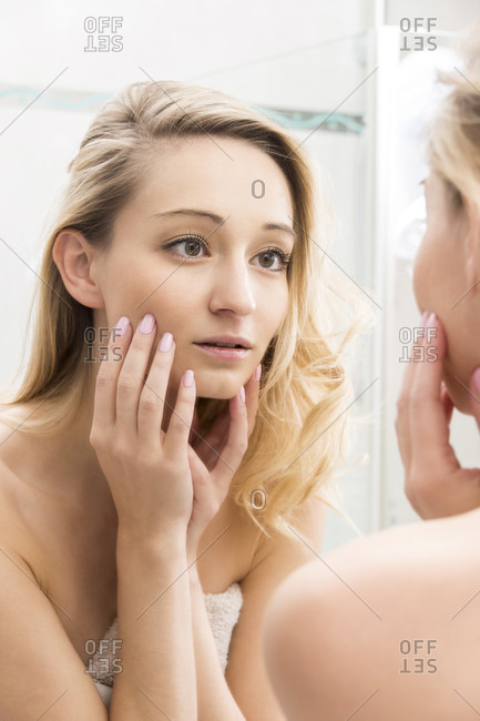 Head and Shoulders Close Up of Young Blond Woman Touching Face and Looking Approvingly at Reflection in Bathroom Mirror