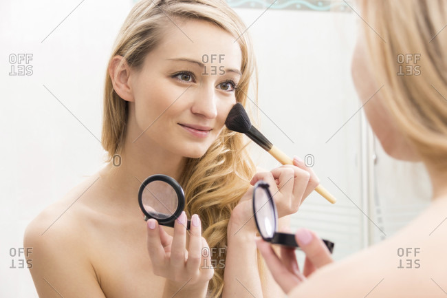 Smiling attractive young blond woman applying blusher to her cheek from a handheld compact using a large cosmetics brush, focus to her reflection in the mirror in a beauty concept