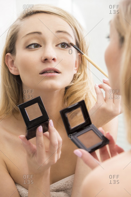 Attractive woman applying eye makeup using a cosmetics brush to apply eye shadow from a small handheld compact, focus to her reflection in the mirror