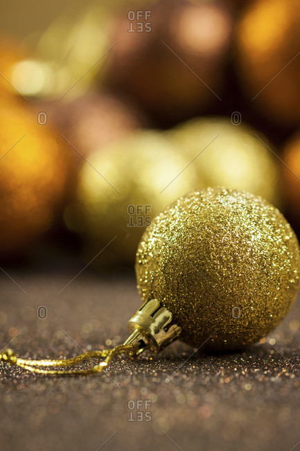 Golden Christmas baubles, background with selective focus to a single glitter ball in the foreground with a blurred pile behind giving a warm ambiance and copyspace for your seasonal greeting