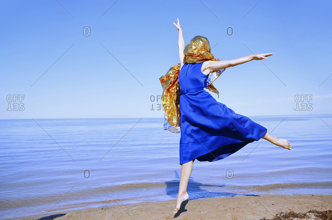 Woman with head wrapped in the golden foil next to the sea
