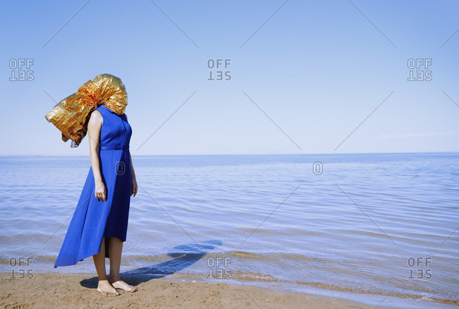 Woman with head wrapped in the golden foil standing at the sea