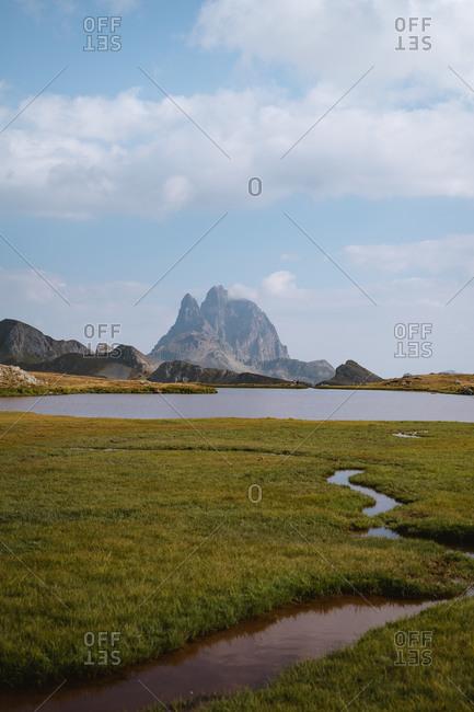 Narrow water stream leading into big rugged mountain