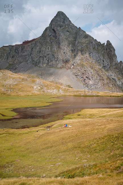 Adult couple sitting on the grass with their dog in front of an alpine lake