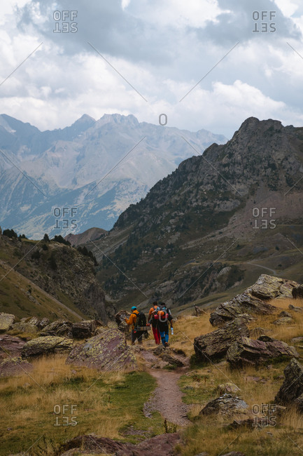 Three hikers carrying mountaineering gear descending a steep hill