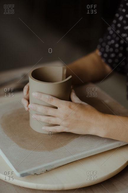 Hands of a woman shaping clay into a cylinder