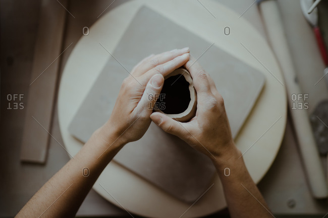 Woman's hands molding clay viewed from above