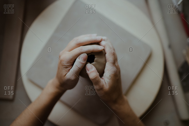 Overhead view of the hands of woman molding clay