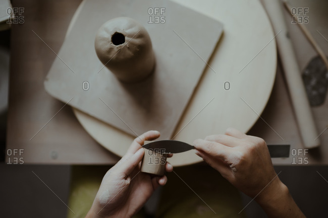 Hands of woman making pottery with tools and clay viewed from above