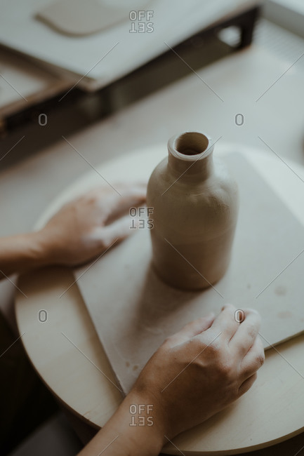 Hands of woman beside molded clay jug