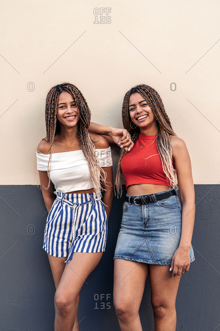 Attractive African American sisters with cool braids smiling and looking at camera