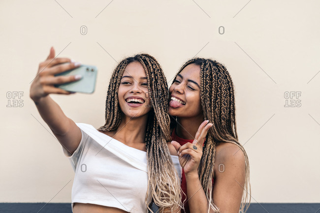 Attractive African American sisters with cool braids smiling and taking selfie in the street