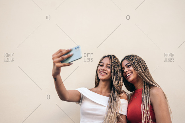 African American sisters with cool braids smiling and taking selfie in the street