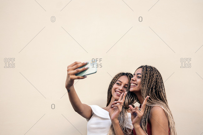 African American sisters with cool braids smiling and making peace signs while taking selfie
