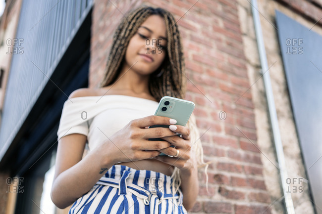 A bottom view young African American woman with braids smiling and using her phone