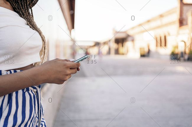 A side view young African American woman with braids using her phone on city street