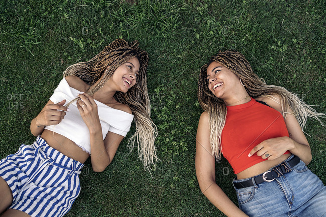 Happy African American sisters with braids having fun and lying on the grass looking at each other