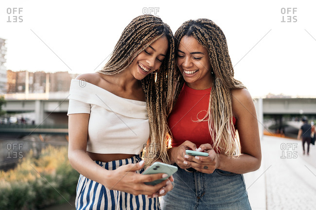 Young African American sisters laughing and using their phones in the street