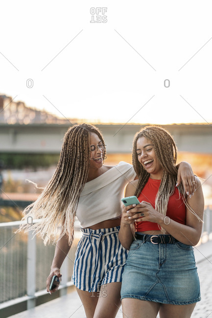 Young African American sisters laughing and using their phones in the street at sunset