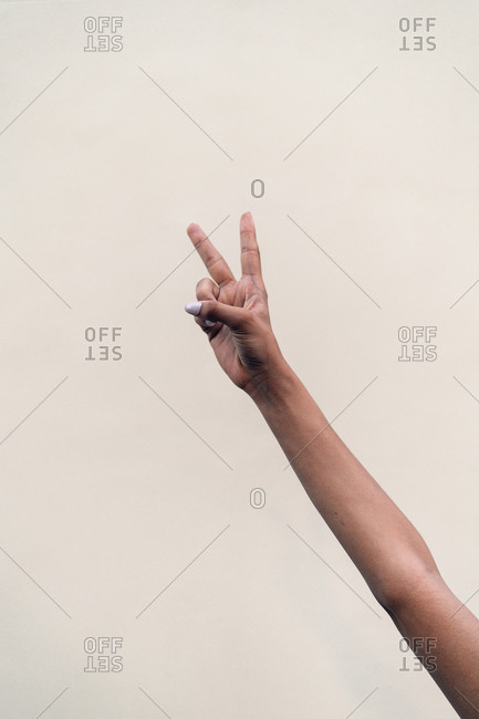 Faceless woman doing the peace sign with her fingers against white wall