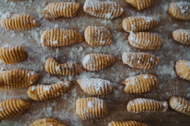 Close up of freshly rolled sweet potato gnocchi on a floured wooden cutting board