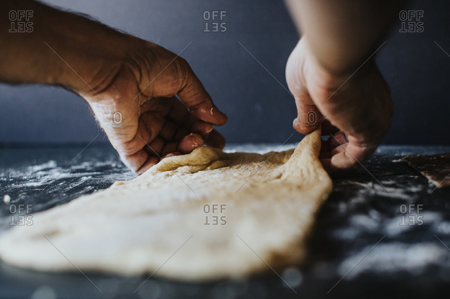 Man stretches dough with hands on top of black floured countertop against a dark background