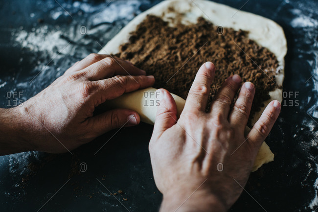 View from above of a man rolling cinnamon babka dough with his hands on a black floured countertop