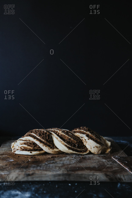 Cinnamon babka loaf before baking on a wooden cutting board on a black floured countertop against a black background