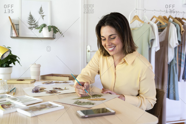 Smiling beautiful woman painting with leaves on cardboard while sitting at table