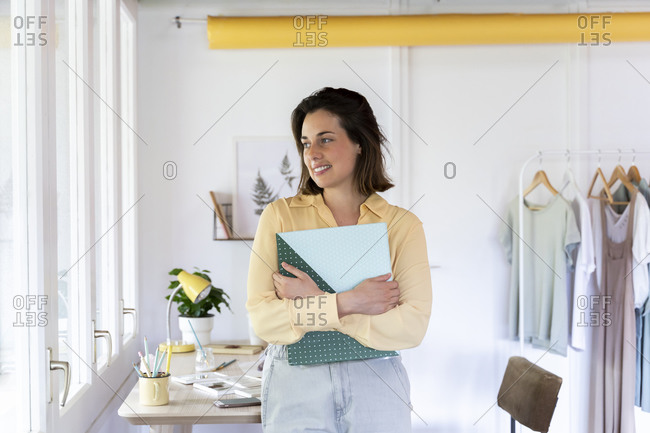 Smiling young female design professional holding file while looking away at clothing store