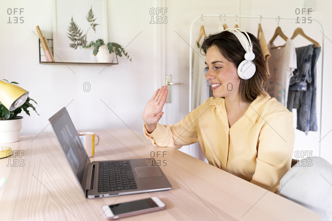 Smiling woman waving to friends on video call through laptop at home