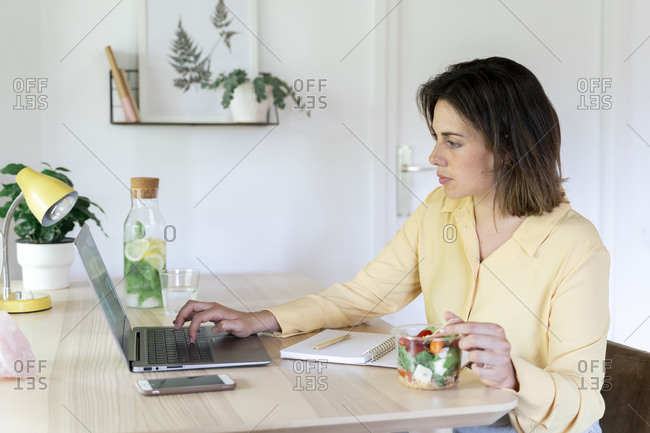 Young businesswoman using laptop while eating healthy salad at table