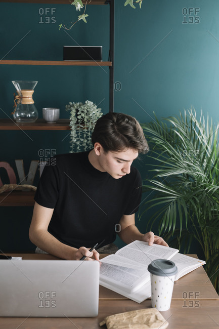 Handsome male student reading book while doing homework at table
