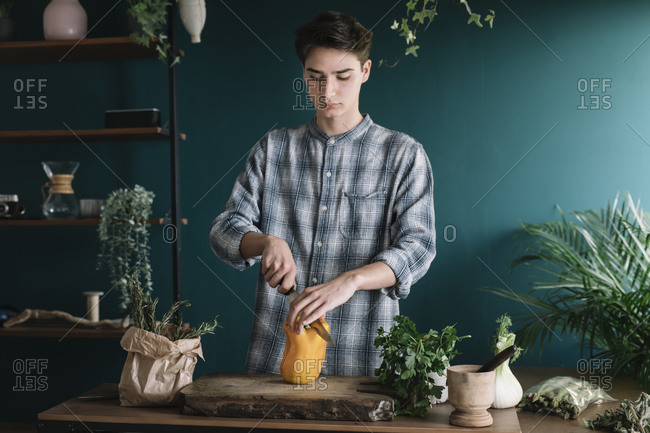 Handsome young man cutting bell pepper on board while standing against green wall