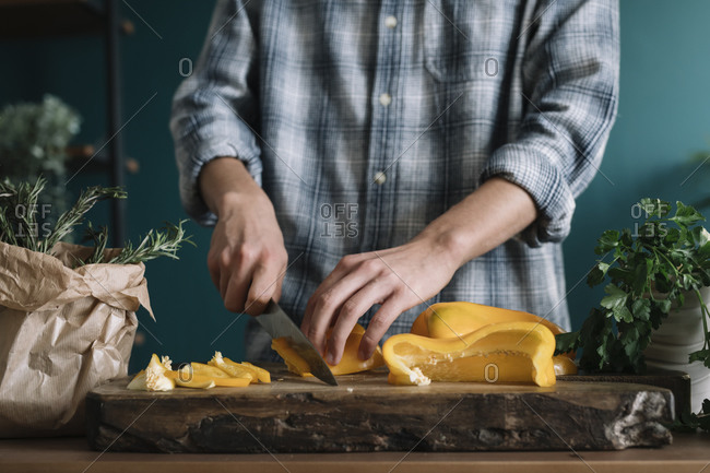 Hands of man cutting yellow bell pepper on board in kitchen