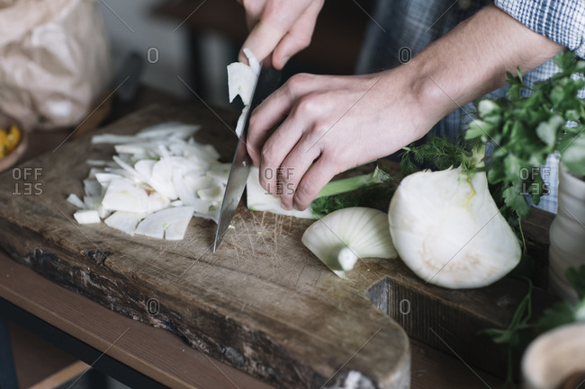 Hands of man cutting fennel on board in kitchen