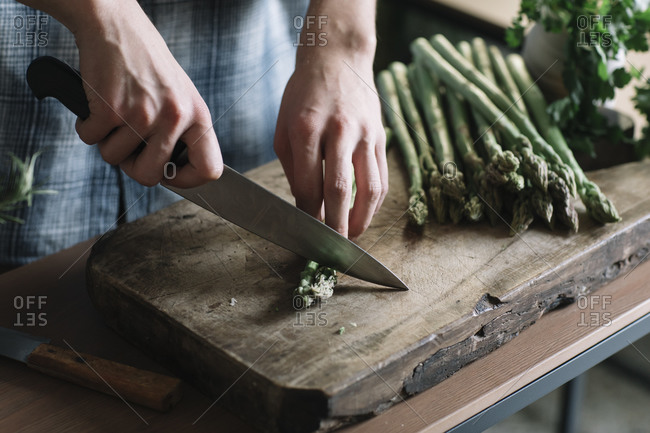 Hands of man cutting fresh asparagus on board in kitchen