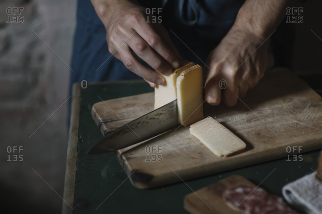 Hands of man cutting artisanal cheese slices on board at table