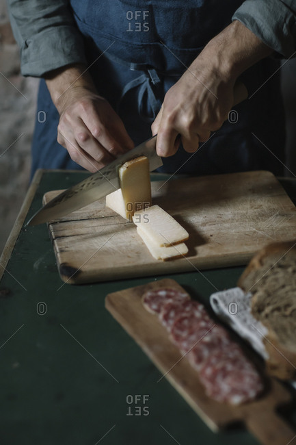 Midsection of young man cutting artisanal cheese slices on board at table