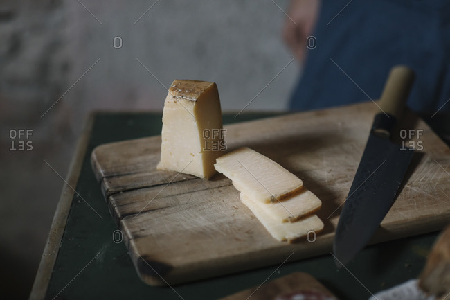 Close-up of artisanal cheese slices with knife on cutting board