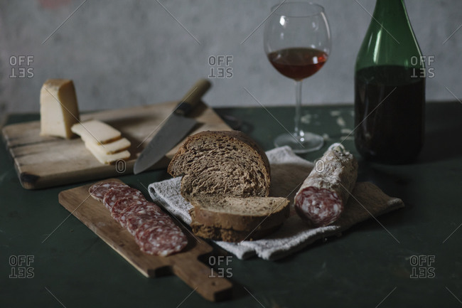 Close-up of fresh salami sausage with homemade bread and wine on table in cellar