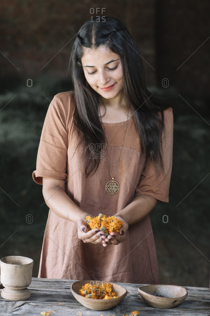 Beautiful woman looking at orange flowers on clasped hands
